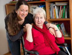 senior woman in a wheelchair together with caregiver