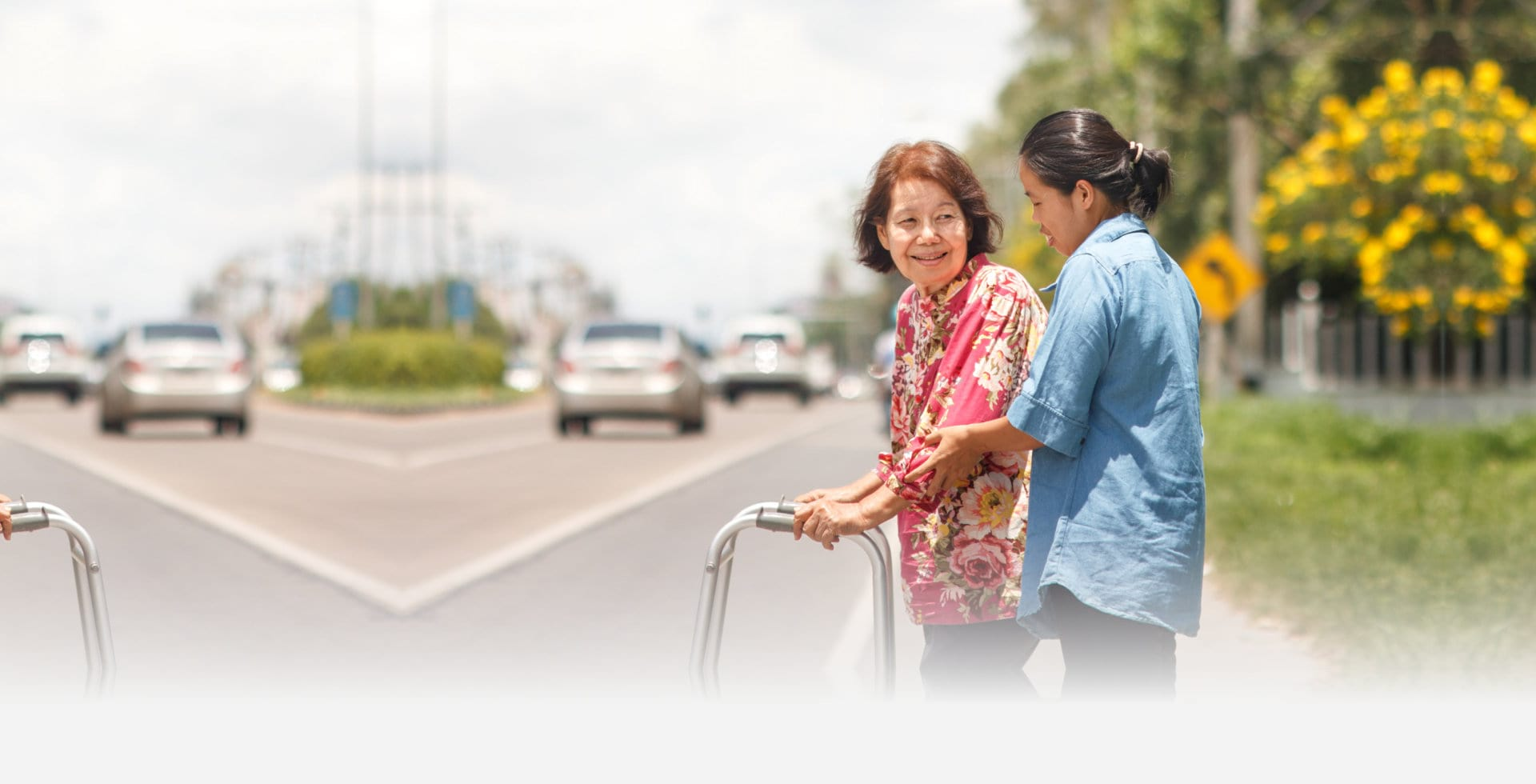 young woman helping senior woman in walking