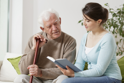 Image of young carer reading book to senior man